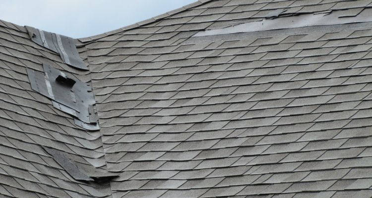 Damaged roof with missing shingles.